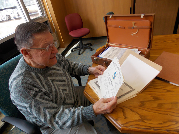 HOWARD BALABAN/STAFF<br /> Richard Turoski looks over one of his many commendations earned while serving parts of four decades as an officer in the U.S. Air Force.