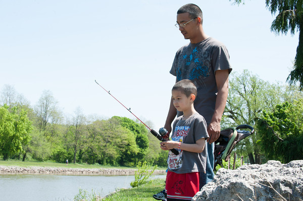 140525 Fishing Derby JOED VIERA/STAFF PHOTOGRAPHER-Lockport, NY-Norberto Negron watches his son Angel Negron (6) fish during thier fishing outing on the canal May 25, 2014.