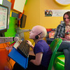 140425 Skyla JOED VIERA/STAFF PHOTOGRAPHER-Buffalo, NY-Beth Dennis(right) watches as her Skyla Dennis plays a computer game in the game room of Roswell Cancer Institute. April 23, 2014.