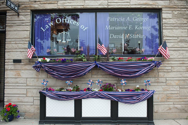 """140523 Purple JOED VIERA/STAFF PHOTOGRAPHER-Lockport NY- the Law offices of Patricia A George are decorated for paint the city purple May 23, 2014. LPT Paint Lockport Purple 052414<br /> Over 30 local businesses decked out their windows and walls with purple decorations for the annual """"Paint the City Purple"""" event to promote next month's American Cancer Society Relay for Life. Many shops and businesses decorated with stars and stripes as well to coordinate with the theme of """"Star-Spangled Relay"""". Mayor Anne McCaffrey announced """"Paint the City Purple Day"""" Friday morning in front of city hall and a panel of five judges scoped out the participants to choose winners. Donna Eick's restaurant won the small business award, First Niagara bank on East Avenue. Tom's Diner won the hospitality award, and the new Canalfront Sandwich shop won the Rookie award."""