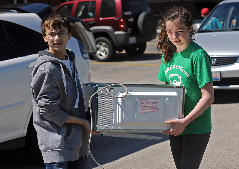 Clarendon Hills, 05/03/14--Andrew Tannebaum and Grace DeAngelis carry a microwave oven from a car to a recycling site they've set up in the school's parking lot. Clarendon Hills Middle School's Eco Club members held an Eco Fair Saturday morning.  | Jon Langham~for The Hinsdalean