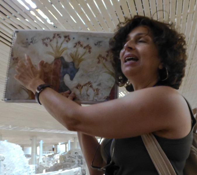 Our Akrotiri guide, Edie, with reproduction of famous wall painting of spring flowers and swallows.