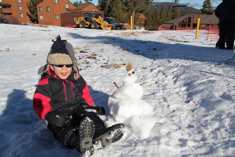 Micah and the snowman he built while waiting for Caleb's skiing lesson