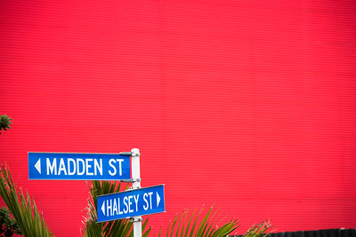 Street signs against a red warehouse.