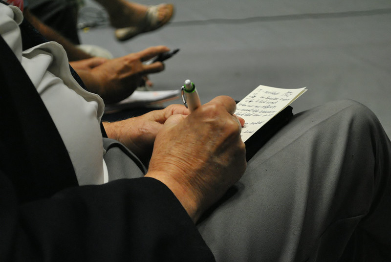 A community member takes notes while Joni Eareckson Tada speaks at dimensions on September 2nd.