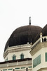This particular mosque is characterized by its dark black domes, rising high over the city streets of Medan.