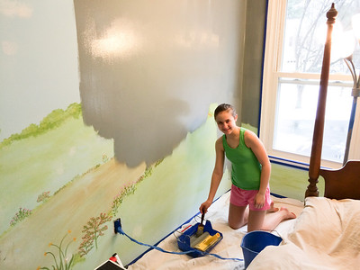 Ainsley painting her bedroom grey.