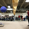 Rob Winner – rwinner@shawmedia.com<br /> <br /> Miguel Gutierrez a member of the Joliet Cyborgs tosses an exercise ball over a wooden barrier which is caught by Zurg, the team's robot, during a demonstration at the Joliet Township High School Administrative Center on Tuesday, Feb. 11, 2014.