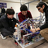 Rob Winner – rwinner@shawmedia.com<br /> <br /> (From left to right) Jake Blaauw, Miguel Gutierrez, and Felipe Reyes of the Joliet Cyborgs prepare their robot, Zurg, before a demonstration at the Joliet Township High School Administrative Center on Tuesday, Feb. 11, 2014.