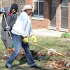 John Patsch - For Shaw Media<br /> Latoya Martin and Crystal Benett rake trash out of the bushes at the Des Plaines Gradens housing complex.