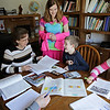Rob Winner – rwinner@shawmedia.com<br /> <br /> Laura Dominick (second from left) helps Rebecca (center), 15, and Anthony, 9, with their assignments as Timmy (left), 13, and Mary Rose (right), 10, work alone at their Minooka home on Tuesday, April 15, 2014.