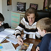 Rob Winner – rwinner@shawmedia.com<br /> <br /> Laura Dominick (center) helps Anthony (right), 9, with a reading lesson as Timmy (left), 13, works alone at their Minooka home on Tuesday, April 15, 2014.