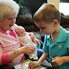 Rob Winner – rwinner@shawmedia.com<br /> <br /> Barbara Brockman holds her 7-week-old grandson Brayden Brockman while helping her 3-year-old grandson Jaxsen Brockman with a puzzle at her son's home in Wilmington Wednesday, June 4, 2014. Barbara Brockman had a stent placed into a partially blocked heart artery during a non-surgical procedure at Presence Saint Joseph Medical Center to help increase blood flow.