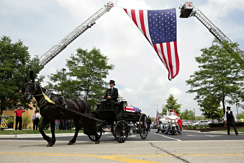 Rob Winner – rwinner@shawmedia.com<br /> <br /> The body of Army Pfc. Aaron Toppen is taken from Parkview Christian Church in Orland Park to St. John's Cemetery on a horse-drawn carriage Tuesday afternoon. The 19-year-old Mokena native was among the five American soldiers killed June 9 in a friendly-fire incident in Afghanistan.<br /> <br /> Orland Park, Ill.<br /> Tuesday, June 24, 2014
