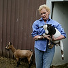 Rob Winner – rwinner@shawmedia.com<br /> <br /> Kim Peters of Calypso Farm in Lockport carries Banana Joe, a Nigerian dwarf goat, from his pen Wednesday, June 11, 2014.