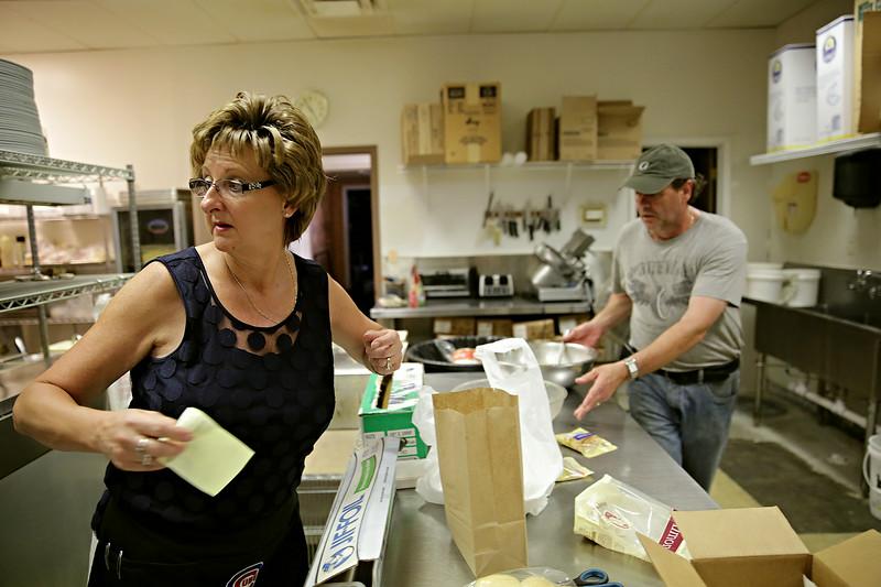 Rob Winner – rwinner@shawmedia.com<br /> <br /> Diana Wysocki (left) and her husband Ed Wysocki work on filling orders in the kitchen of Pub Grub at American Legion Post 1080 in Joliet on Wednesday, June 18, 2014.