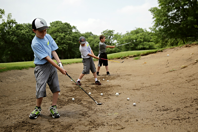 Rob Winner – rwinner@shawmedia.com<br /> <br /> The First Tee participants including Thomas Jackson, 9, Jack Feigl, 9, and Zachary vonPerbandt, 11, practice hitting balls out of the sand at Inwood Golf Course in Joliet Thursday, June 19, 2014.