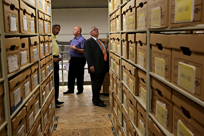 Rob Winner – rwinner@shawmedia.com<br /> <br /> Will County Board Speaker Herb Brooks, Jr. (left) and Will County Board member Mike Fricilone (right), who represents District 7, peer down an aisle of archives while listening to Mike Thompson (center) during a tour of the Nicholson Street Facility in Joliet Tuesday, July 8, 2014.