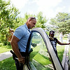 Rob Winner – rwinner@shawmedia.com<br /> <br /> Officer Eric Bernhard of the Neighborhood-Oriented Policing Team helps resident Krista Byes unlock her vehicle after Byes locked her keys inside on the 600 block of North Hickory Street in Joliet Wednesday, July 9, 2014.