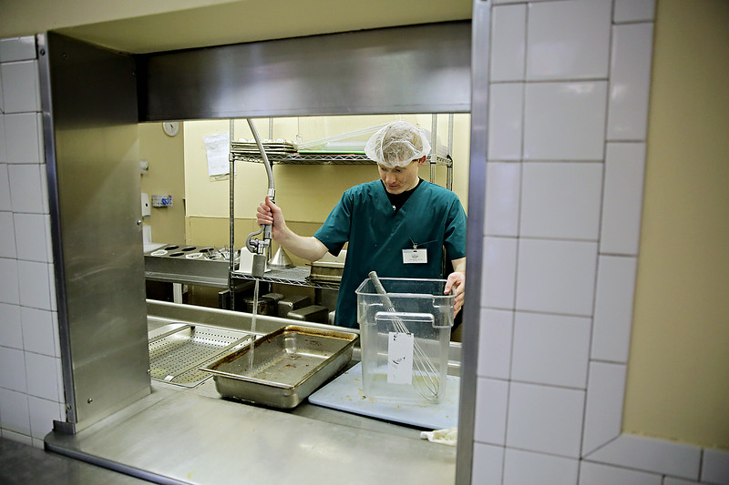 Rob Winner – rwinner@shawmedia.com<br /> <br /> Anthony Cornoyer cleans dishes in the kitchen before dinner is served at Joliet Terrace Wednesday, July 9, 2014. Cornoyer, 22, a dietary aid for Joliet Terrace, received help landing the position from Cornerstone Services, Inc.