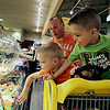Rob Winner – rwinner@shawmedia.com<br /> <br /> (From front to back) Twins Ryan and Cameron Yanak, 4, look over a variety of cookies near the bakery while checking out the grand opening of Mariano's in Shorewood with their father Paul Yanak on Tuesday, July 15, 2014.