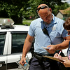 Rob Winner – rwinner@shawmedia.com<br /> <br /> Officer Eric Bernhard of the Neighborhood-Oriented Policing Team helps Maria Janovsky, a landlord, with some paperwork in Joliet Wednesday, July 9, 2014.