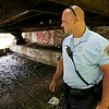 Rob Winner – rwinner@shawmedia.com<br /> <br /> Officer Eric Bernhard of the Neighborhood-Oriented Policing Team checks for activity underneath a railroad bridge near the Des Plaines River in Joliet Wednesday, July 9, 2014.