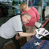 John Patsch-For Shaw Media<br /> Paul Pastell signs the Wounded Warrior Mustang while his wife, Karen, watches.  Pastell is a war vet.