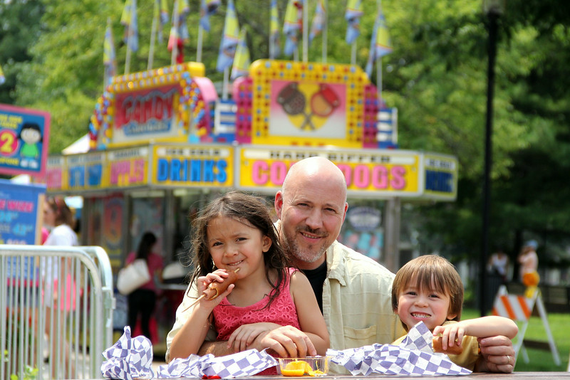 Christine Muilenburg - For Shaw Media     Mai and Lolo Pankuch, 6 and 4, with their dad Mark, take a break from the carnival rides to feast on corn dogs on Saturday, July 19, 2014 during Plainfield Fest.  Plainfield Fest continues Sunday, July 20, 2014.
