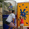 Christine Muilenburg - For Shaw Media    Sophomore athlete Bri Smith, sits in the Plainfield Central HS Athletic Boosters dunk tank, while Sophomore athlete Kamrin Dolbee, assists a young lady on Saturday, July 19, during Plainfield Fest.
