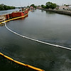 Rob Winner – rwinner@shawmedia.com<br /> <br /> Booms have been placed in the Des Plaines River near the Jackson Street Bridge in Joliet to contain diesel fuel that has been leaking from a sunken tugboat.<br /> <br /> Friday, Aug. 8, 2014