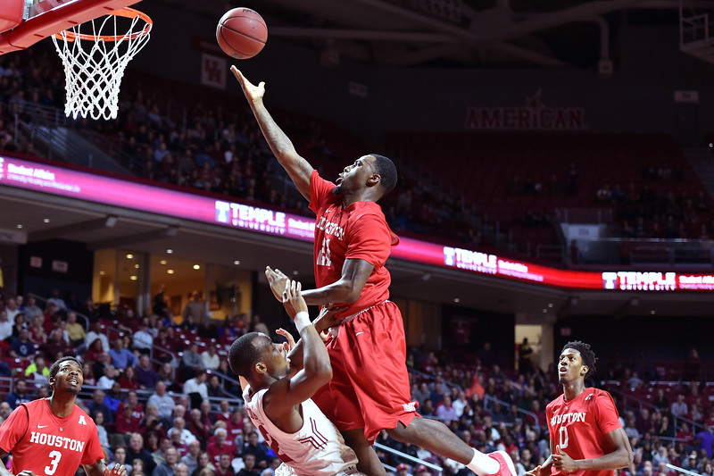 PHILADELPHIA - FEBRUARY 26: Houston Cougars guard Jherrod Stiggers (21) crashes into Temple Owls guard Will Cummings (2) drawing a charging call during the AAC conference college basketball game  February 26, 2015 in Philadelphia.