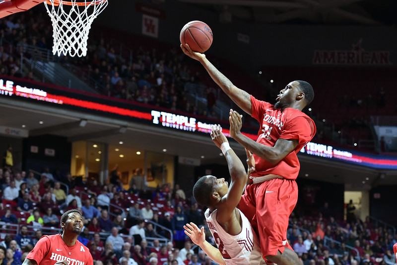PHILADELPHIA - FEBRUARY 26: Temple Owls guard Will Cummings (2) draws a charging foul as Houston guard Jherrod Stiggers (21) crashes into him during the AAC conference college basketball game  February 26, 2015 in Philadelphia.