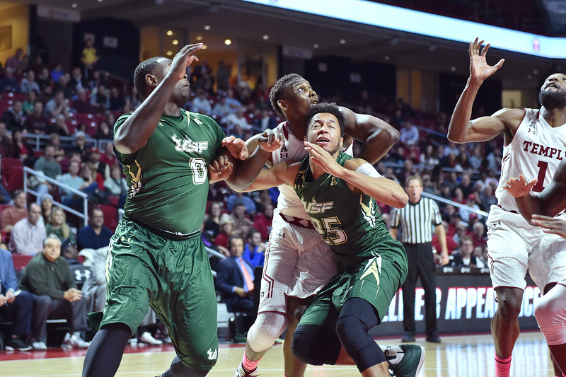 PHILADELPHIA - JANUARY 22: South Florida Bulls guard Troy Holston Jr. (25) grimaces as he slams into Temple Owls guard Daniel Dingle (4) during the AAC conference college basketball game January 22, 2015 in Philadelphia.