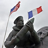 A sailor holds a shell as the American and French flags wave in the wind above the U.S. Navy monument on Utah Beach. The monument was unveiled in 2008.