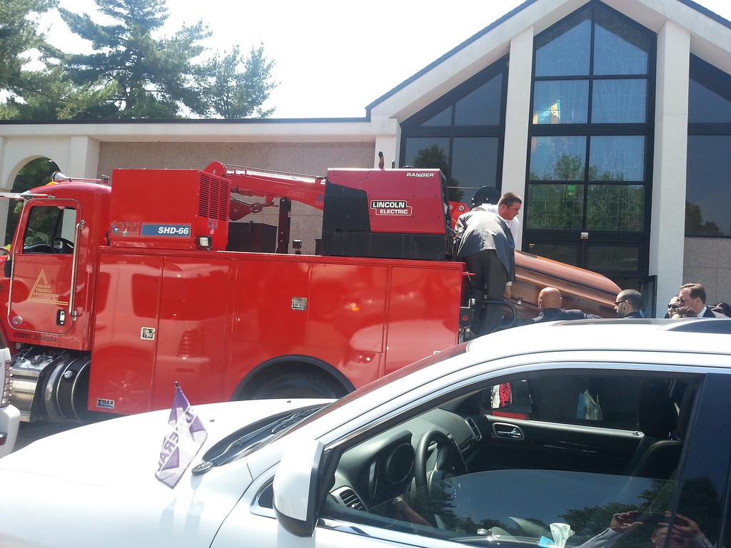Leoni's sons placing the casket in his grandson's mechanics truck.