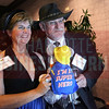Vianne Howitt and Ivan Howitt, PhD with InfoSense, Inc. pose in a photo booth with their company mascot, a super hero rat.