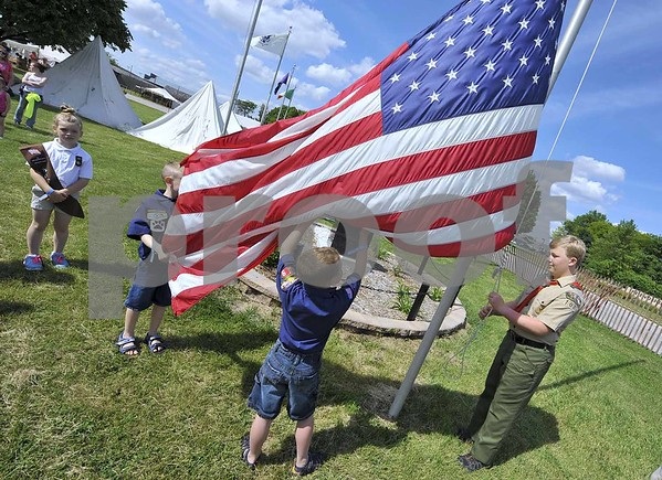 -Messenger photo by Hans Madsen<br /> <br /> The 41st annual Frontier Days Celebration at the Fort Museum kicked off Friday afternoon with a flag raising by local Scouts. At left, Alix Lawler, 7, and Brayden Schuster, 7, both with Fort Dodge Cub Scout Pack 19, hold onto the flag as Boy Scout Elijah Collins, 12, with Humboldt Troop 108, works the rope. Girl Scout Brownie Aianna Kirby, 6, with Fort Dodge troop 57, watches at left.
