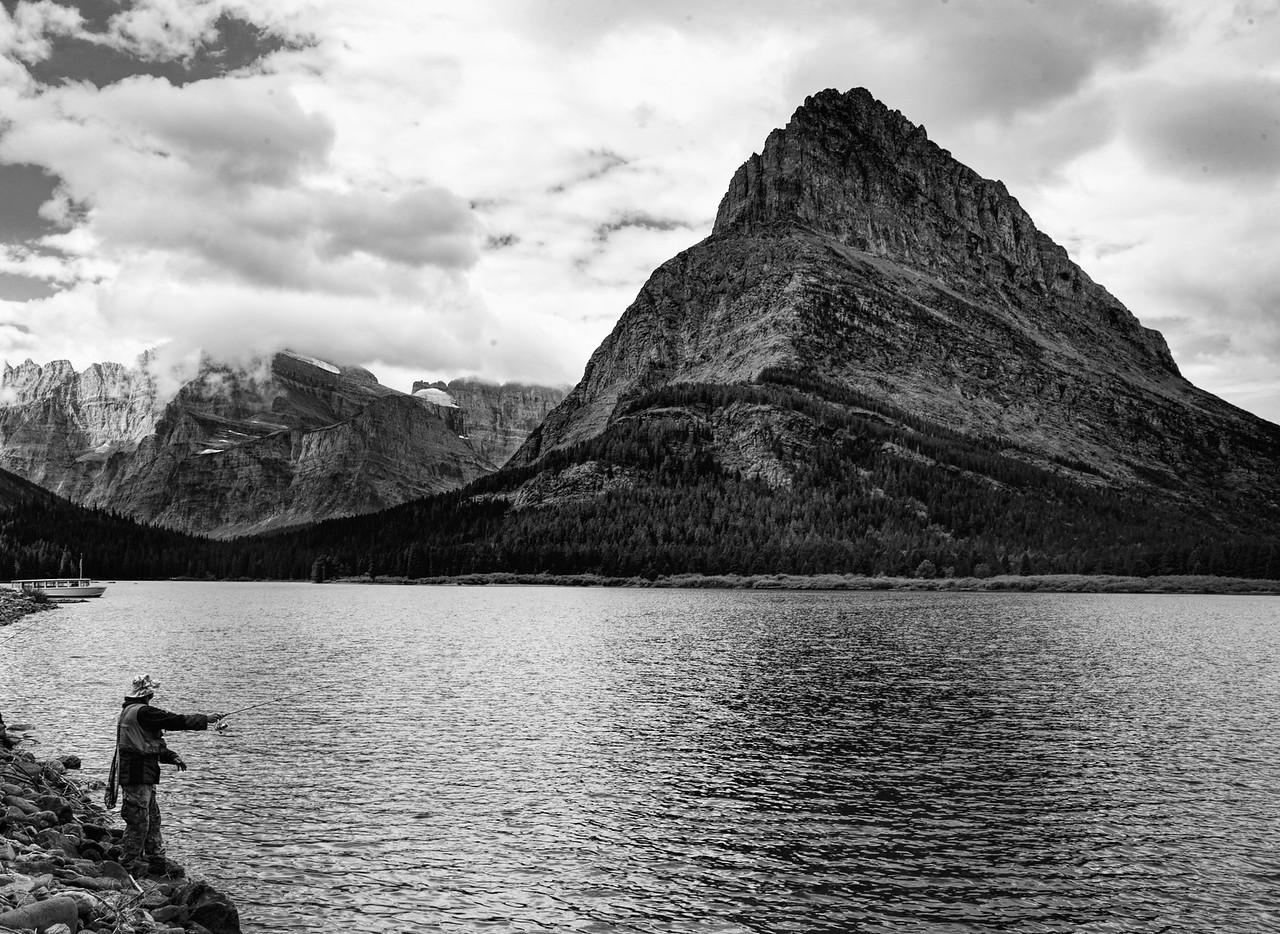 Fisherman at Many Glacier Lake b&w