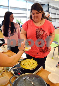 4/1/2015 Mike Orazzi | Staff Allison LaFleur gets a sample cooking demonstration by sisters Tina Autunno and Rosa Rocco for the French/Italian Club at Plainville High School on Wednesday.