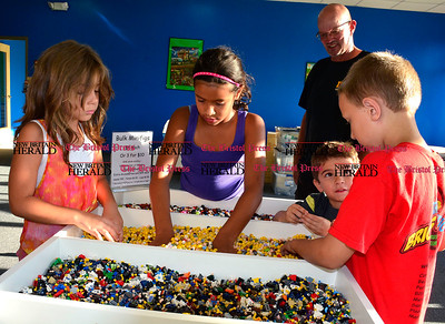 9/16/2015 Mike Orazzi | Staff Jayda Koch, and her sister Alivia and brother Joseph look through a bin of loose Legos with Ethan Schneider at the opening of the Bricks & Minifigs store on Queen Street in Southington on Wednesday evening.