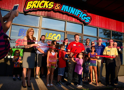 9/16/2015 Mike Orazzi | Staff Rob Schneider cuts the ribbon at the opening of the Bricks & Minifigs store on Queen Street in Southington on Wednesday evening.