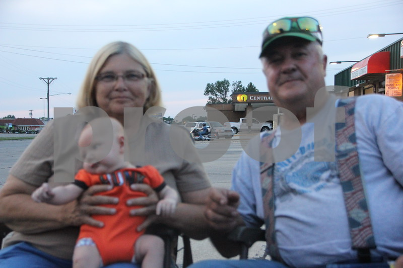 Seen here is  (left to right) : Colleen Eslick, baby Ryker  Eslick (in lap), and Rich Eslick,  one of the owners of a late model car (car not pictured)that brought their car to the Ja-Mars Cruise night to share with other car enthusiasts present at the event that was held at Jar-Mars in Fort Dodge. The event took place on Friday, August 7, 2015. Little Ryker may have been  the youngest to  attend the event.