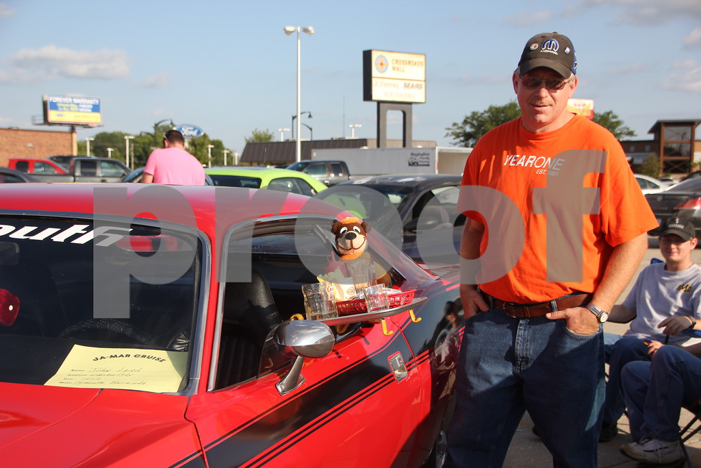 On Friday, August 7, 2015, Ja-Mars in Fort Dodge held the Cruise  night, where a large number of  cars were present with their owners to share with car enthusiasts. Seen here is: John Laird of Webster City  with his 1973 Plymouth Barracuda adding some A &. W drive-in memorabilia for extra touch.