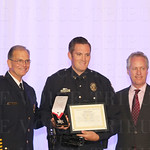 Chief of Police Steve Conrad, Medal of Valor awardee Officer Steven McAtee and Mayor Greg Fischer.