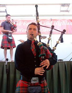 Jessie Ofgang looking wistful while playing the great highland pipes.  Brother Levon in the background.