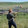 Girl swings lariat in corral