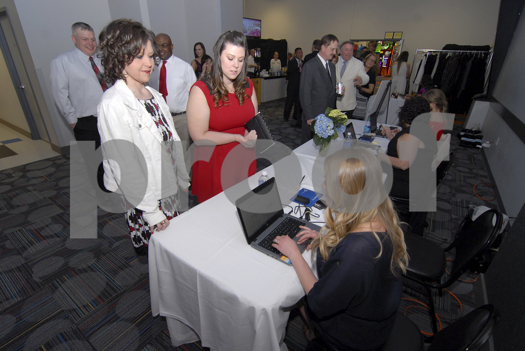 -Messenger photo by Hans Madsen<br /> <br /> Kassi Wessing, with the American Heart Association, gets Julie Wooster, left, and Jessica Meyer, center, both of Fort Dodge, checked into the 18th annual Sweetheart Gala in the Cardiff Center at Fort Frenzy.