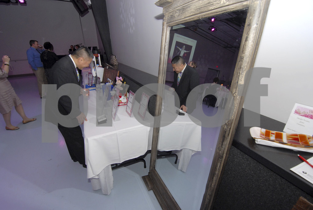 -Messenger photo by Hans Madsen<br /> <br /> Dr. Michael Lee, and his reflection, check out some of auction items Saturday night during the 18th annual Sweetheart Gala in the Cardiff Center at Fort Frenzy.