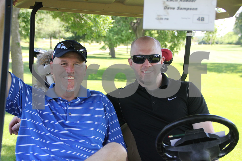 (right to left) Zach Roeder and Greg Sampson jump in the cart to head to their next hole at the 18 hole course where the Swing for A Cure event took place on Friday, June 19, 2015. The event took place at the Fort Dodge Country Club.